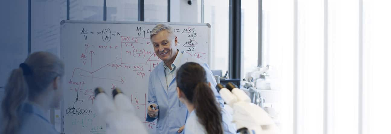 Science professional next to a whiteboard